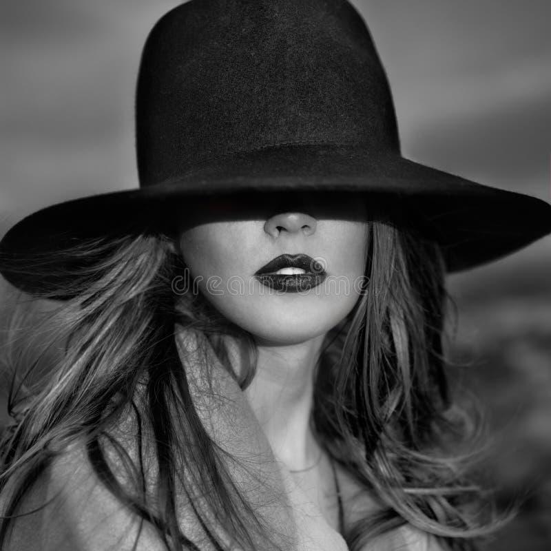 Zwart-wit portret van elegante mooie vrouw die een hoed dragen royalty-vrije stock foto