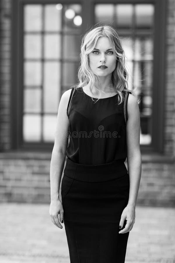 Zwart-wit portret van ernstige elegante jonge blondevrouw royalty-vrije stock afbeelding