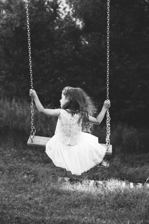 Zwart-wit portret van het leuke meisje glimlachen op schommeling bij de zomerdag, Gelukkig kinderjarenconcept royalty-vrije stock foto's