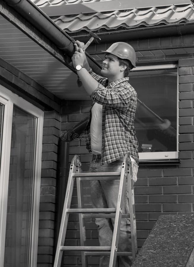 Zwart-wit portret van mannelijke timmerman die huisdak herstellen stock afbeelding