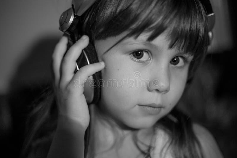 Zwart-wit portret van meisje in hoofdtelefoons Meisje het luisteren muziek royalty-vrije stock afbeelding