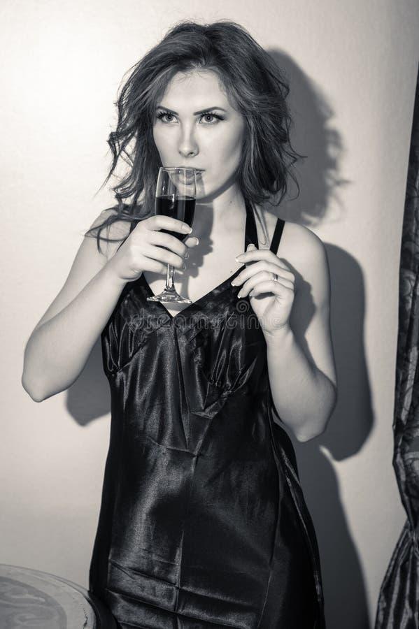 Zwart-wit portret van mooie jonge dame met een glas van drank op lichte achtergrond stock fotografie