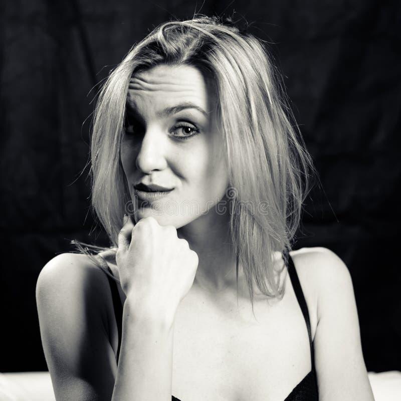 Zwart-wit portret van nieuwsgierige jonge vrouw stock foto