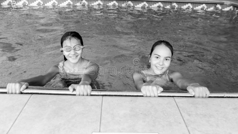 Zwart-wit portret van twee gelukkige glimlachende tieners die in binnen zwembad stellen royalty-vrije stock afbeelding