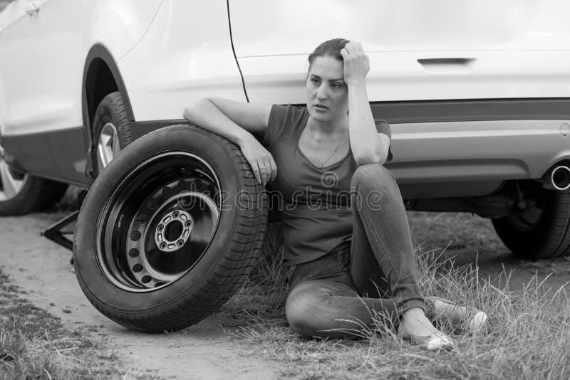 Zwart-wit portret van verstoord jong vrouwen leunend auto extra wiel en het wachten op de autodienst stock afbeeldingen