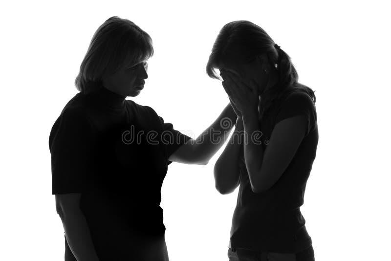 Zwart-wit silhouet van een houdende van moeder die het meisje in nood troost royalty-vrije stock afbeelding