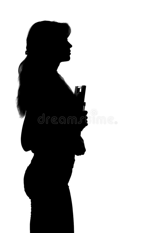 Zwart-wit silhouet van een jonge vrouwelijke student met een omslag en een pen ter beschikking stock fotografie