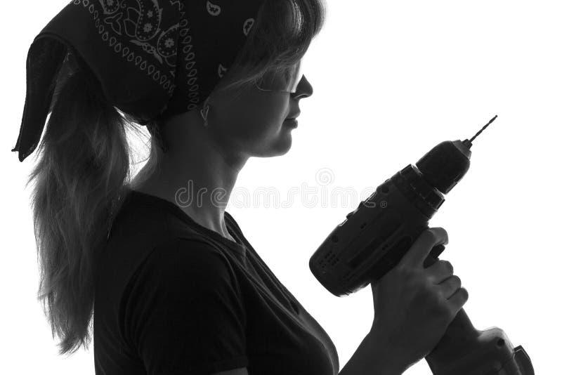 Zwart-wit silhouet van een jonge vrouwenbouwvakker in overall met een schroevedraaier in zijn handen en beschermende brillen en b stock fotografie