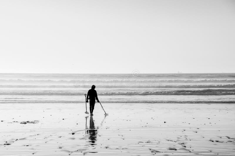 Zwart-wit silhouet van een mannetje die een metaaldetector met behulp van die naar schat at low tide zoeken royalty-vrije stock foto