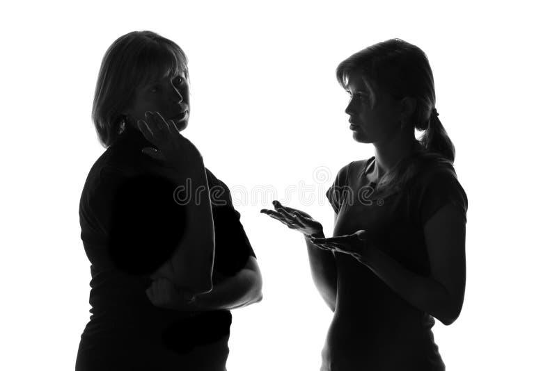 Zwart-wit silhouet van een meisje dat zijn moeder over de problemen en het wachten op de raad vertelt stock foto