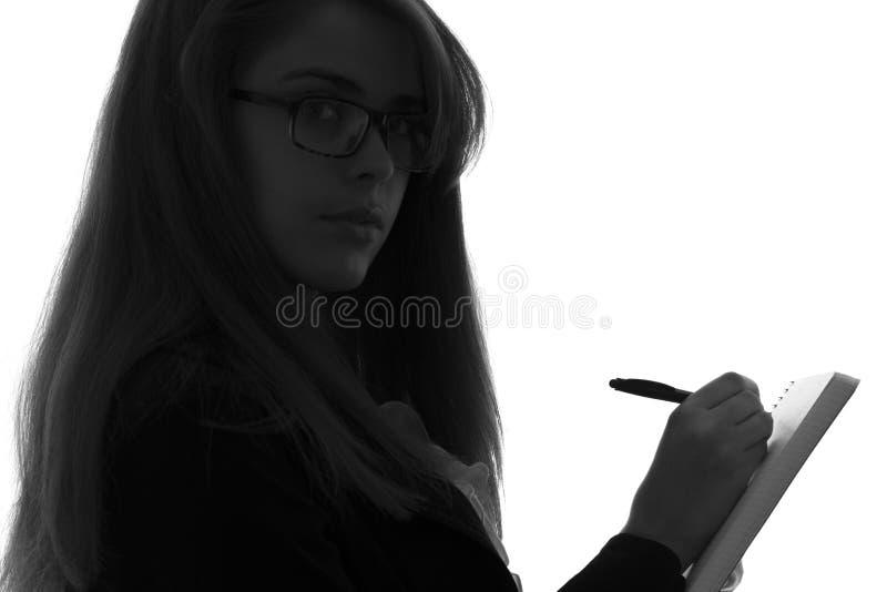zwart-wit silhouet van een vrouw in een bureau met een omslag voor bladen werken en een pen die in de handen stock foto