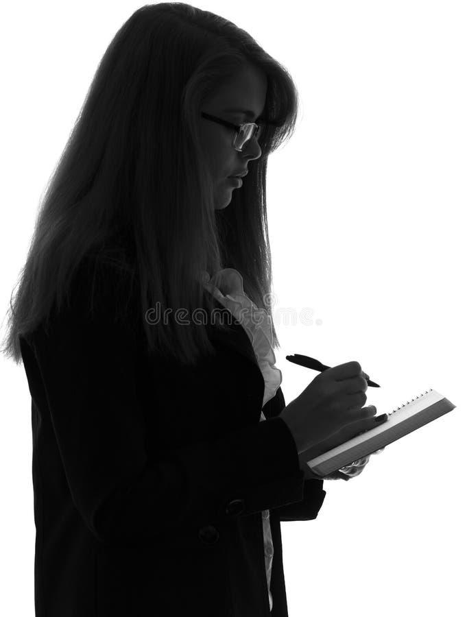 zwart-wit silhouet van een vrouw in een bureau met een omslag voor bladen werken en een pen die in de handen stock fotografie