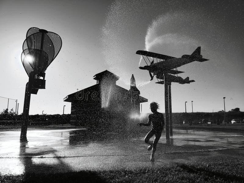 Zwart-wit silhouet van het peuter het meisje van het jong geitjekind bespatten met water van sproeier bij speelplaats royalty-vrije stock afbeeldingen