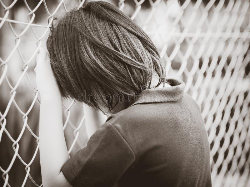 Zwart-wit van het knappe droevige de omheiningsnetwerk van de jongensholding opleveren Emotiesconcept royalty-vrije stock afbeeldingen