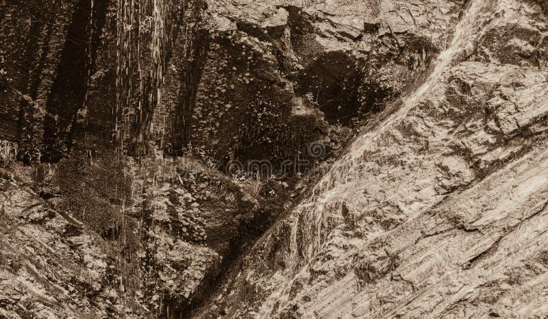 Zwart-wit van water die onderaan rotsachtige richel stromen royalty-vrije stock foto