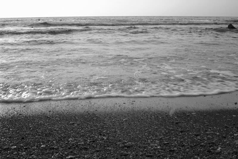 Zwart-witte de zomerachtergrond van heet zand met overzees of oceaangolfbellen stock afbeelding