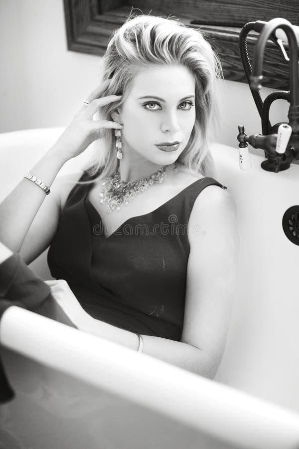 Zwart-witte dichte omhooggaand van een blonde vrouw in een uitstekende ton met een zwarte kleding stock afbeeldingen
