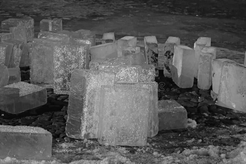 Zwart-witte die Ijsblokken, op de rivierbank worden gekubeerd stock afbeeldingen