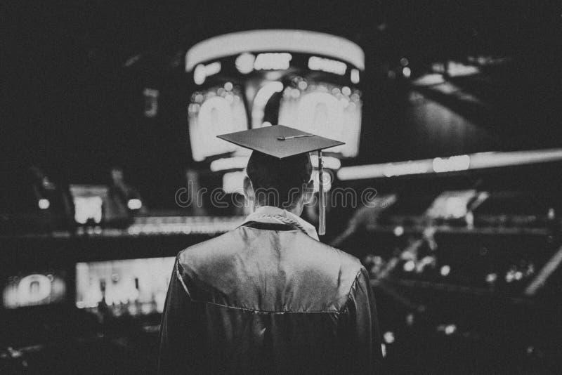 Zwart-witte die rug van een student wordt geschoten die in een grote zaal een diploma behalen die een graduatietoga dragen stock afbeelding