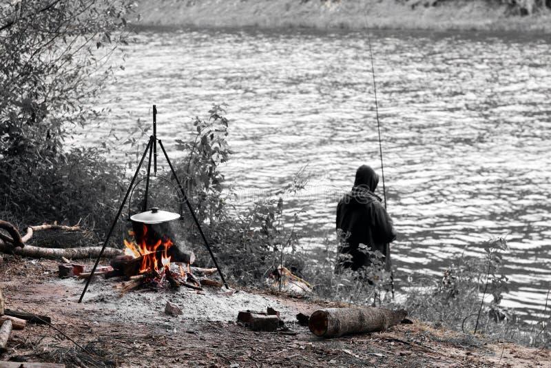 Zwart-witte foto die visser, brand met driepoot afschilderen en pot voor het koken in de herfst koken royalty-vrije stock afbeeldingen