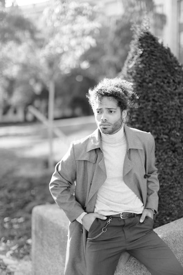 Zwart-witte foto van de afro Amerikaanse mens die zich in park dichtbij struik bevinden royalty-vrije stock afbeeldingen