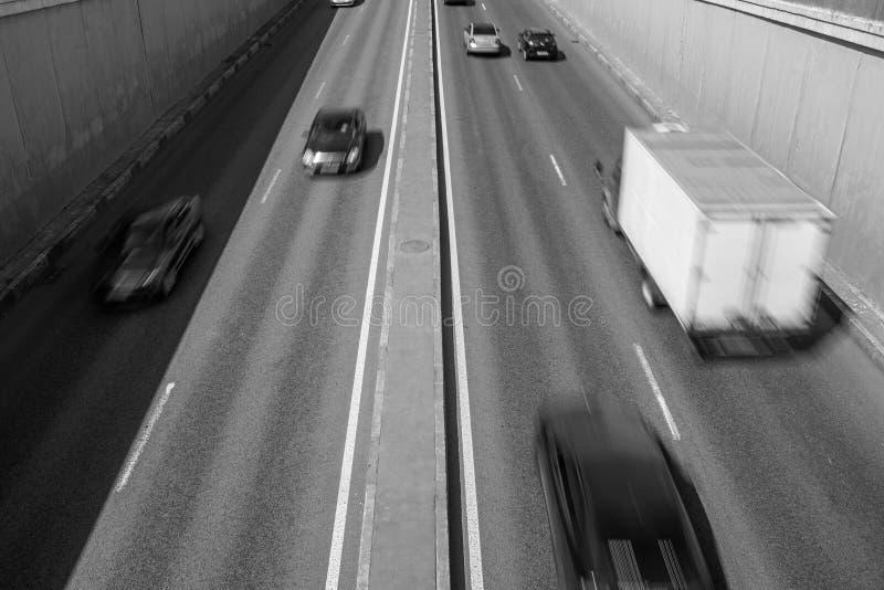 Zwart-witte foto van de weg met auto's in motie stock fotografie