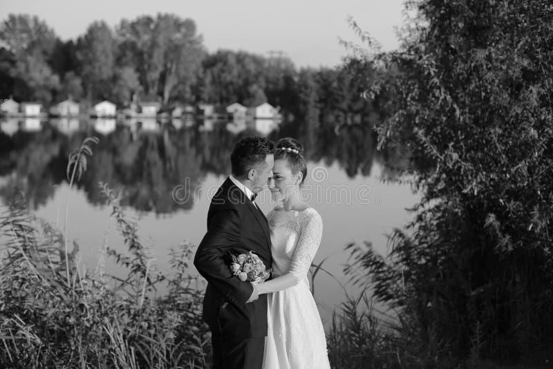 Zwart-witte foto van een bruid en een bruidegom dichtbij meer royalty-vrije stock foto's