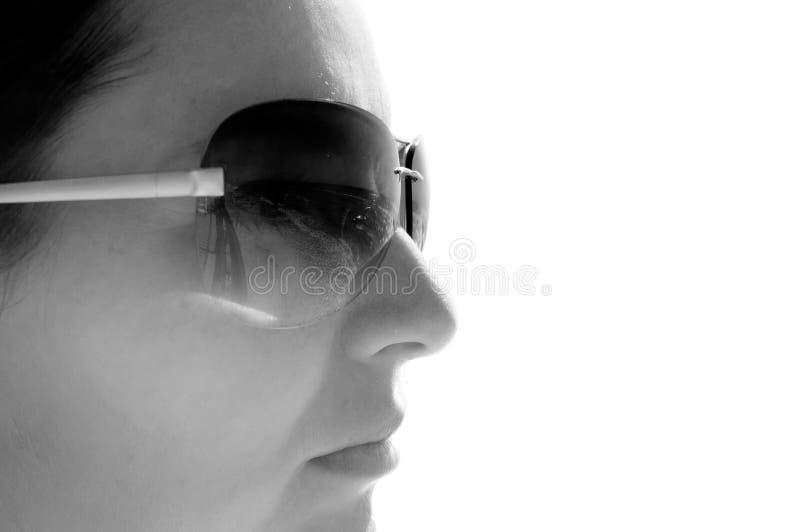 Zwart-witte foto van een meisje in profiel in zonnebril copyspace stock afbeelding