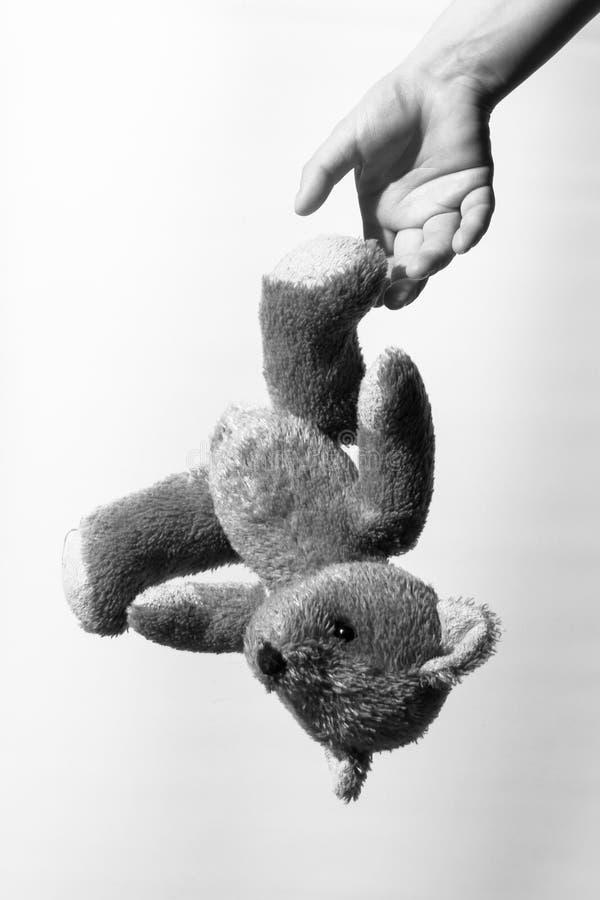 Zwart-witte foto van een meisjes` s hand die een teddybeer werpen stock foto