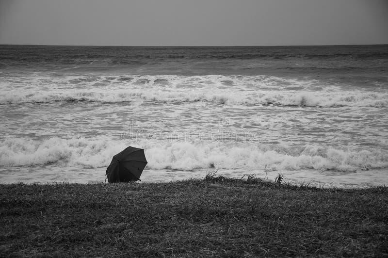 Zwart-witte foto van een paraplu die op de kust van een stormachtige overzees liggen royalty-vrije stock fotografie