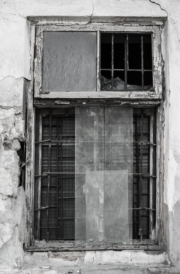 Zwart-witte foto van een raamkozijn met gedeeltelijk gebroken vensters en metaalbars binnen de oude dilapidated muur royalty-vrije stock fotografie