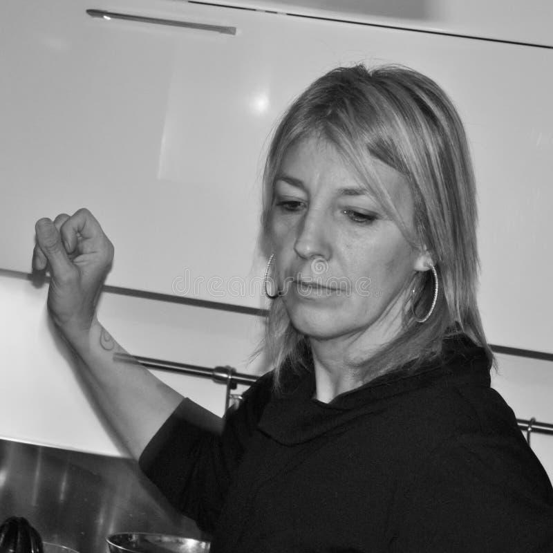 Zwart-witte foto van een vrouw in de keuken met peinzende uitdrukking stock foto's