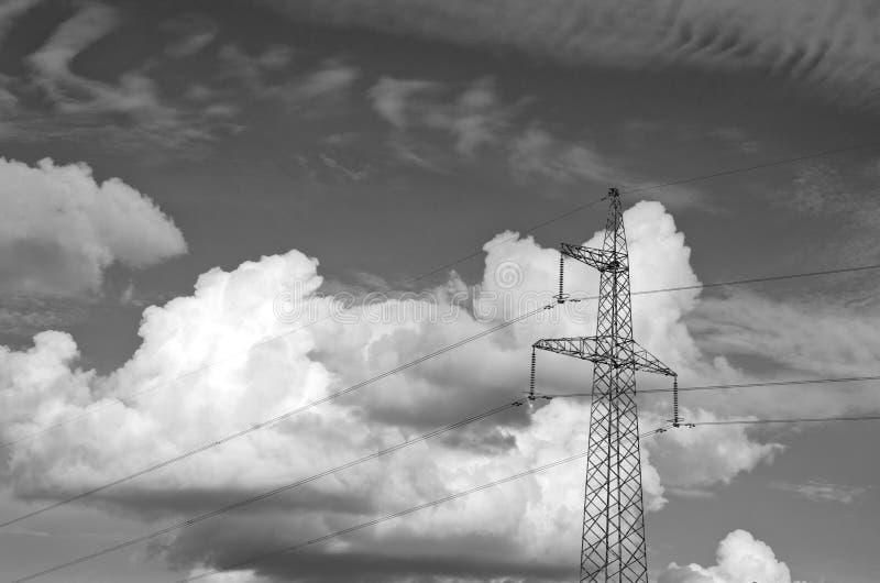 Zwart-witte foto van elektropyloon met dramatische wolken stock afbeelding