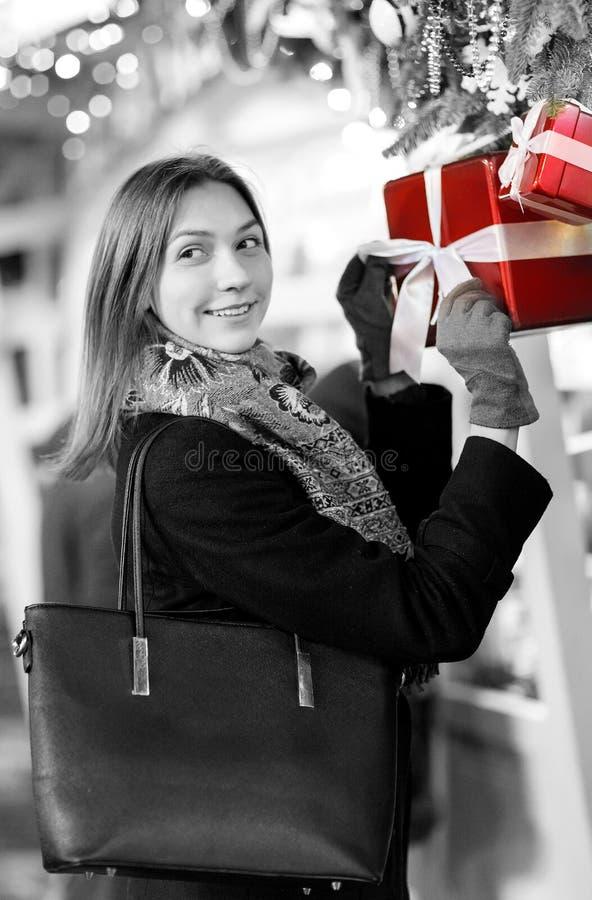 Zwart-witte foto van gelukkige vrouw met glas in handen dichtbij dozen met giften royalty-vrije stock afbeelding