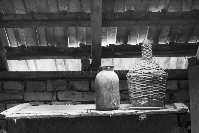 Zwart-witte foto van glas, houten en metaalvoorwerpen in de zolder stock foto's