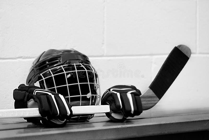 Zwart-witte foto van hockeymateriaal op de bank: Helm, handschoenen en stok royalty-vrije stock afbeelding