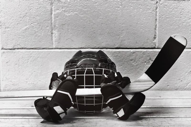 Zwart-witte foto van hockeytoebehoren: helm, stok, handschoenen stock fotografie