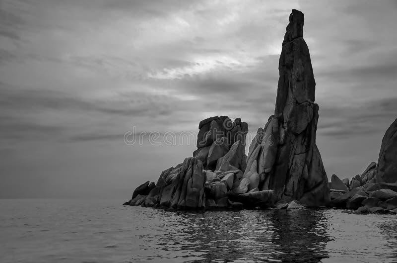 Zwart-witte foto van kleine rotsen op de vreedzame kust in de vorm van een mens stock foto's