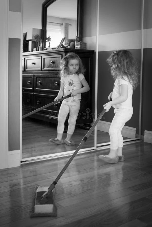 Zwart-witte foto van weinig wit meisje Het meisje helpt om het huis schoon te maken Zij houdt een zwabber royalty-vrije stock foto's