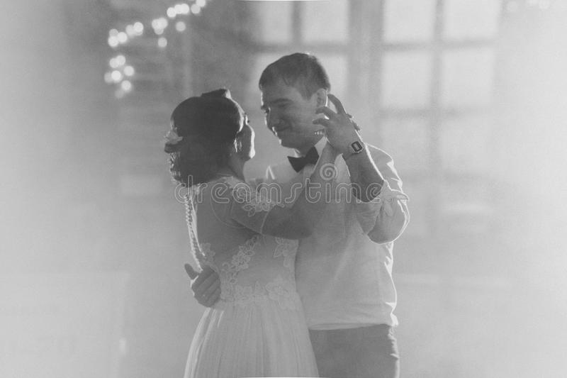 Zwart-witte fotobruid en bruidegom die de eerste dans op de onscherpe achtergrond dansen stock foto's