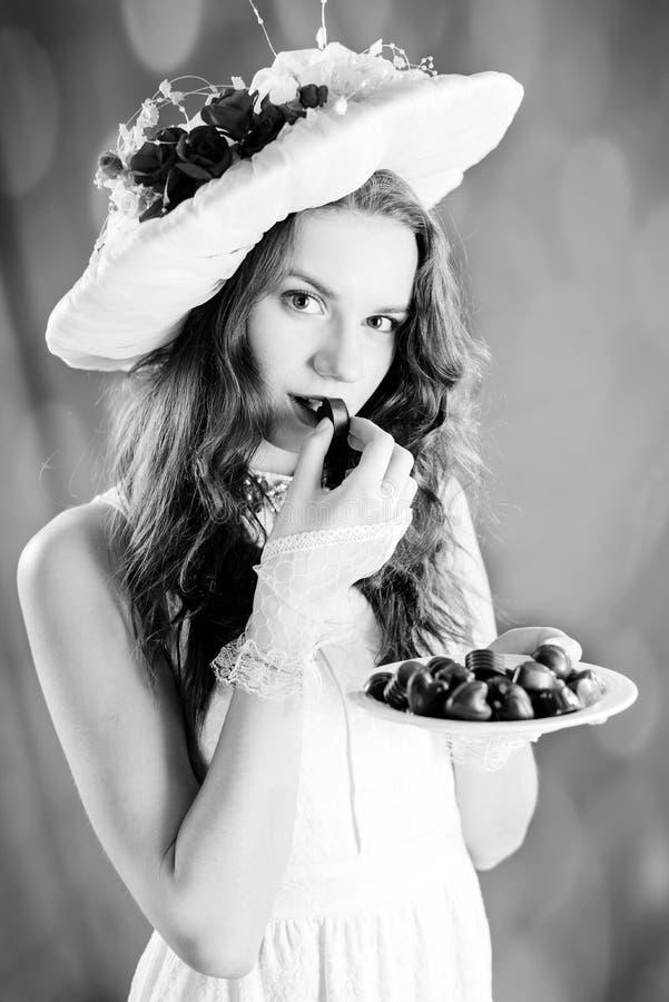 Zwart-witte fotografie van mooie elegante dame met chocolade royalty-vrije stock fotografie