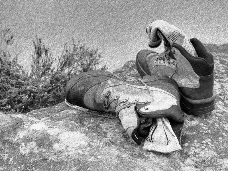 Zwart-witte gestormde retro schets Wandelaar hoge laarzen en zwetende grijze sokken Het rusten op de kei bij stroom royalty-vrije stock afbeeldingen