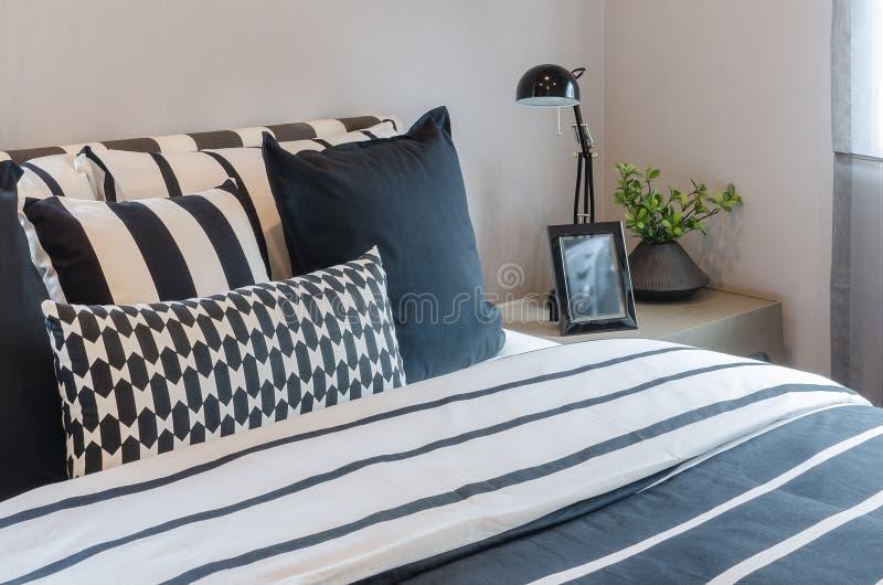 Zwart-witte hoofdkussens en deken op bed met zwarte lamp op Ta royalty-vrije stock afbeelding