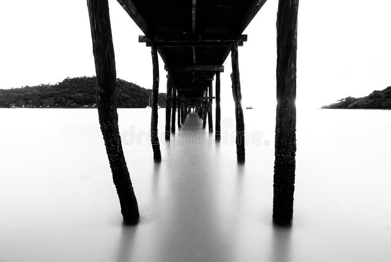 Zwart-witte houten brug stock afbeelding
