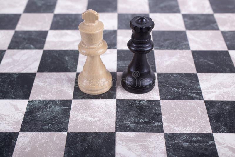 Zwart-witte houten koningen op schaakbord stock foto