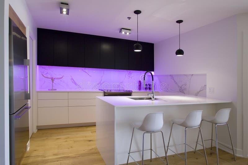 Zwart-witte keuken met eiland en krukken stock afbeelding