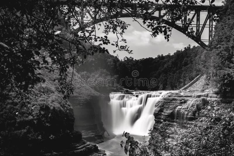 Zwart-witte landschapsfoto van Hogere waterval in Letchworth-het Park van de Staat, Staat New York, de V.S. De brug is over de wa royalty-vrije stock fotografie