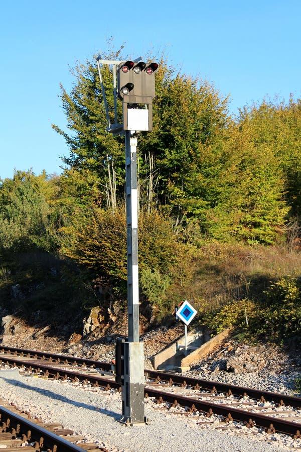 Zwart-witte lange die metaalpool met de lichten van het spoorwegsignaal op bovenkant met grint en spoorwegsporen met dichte bomen stock foto's