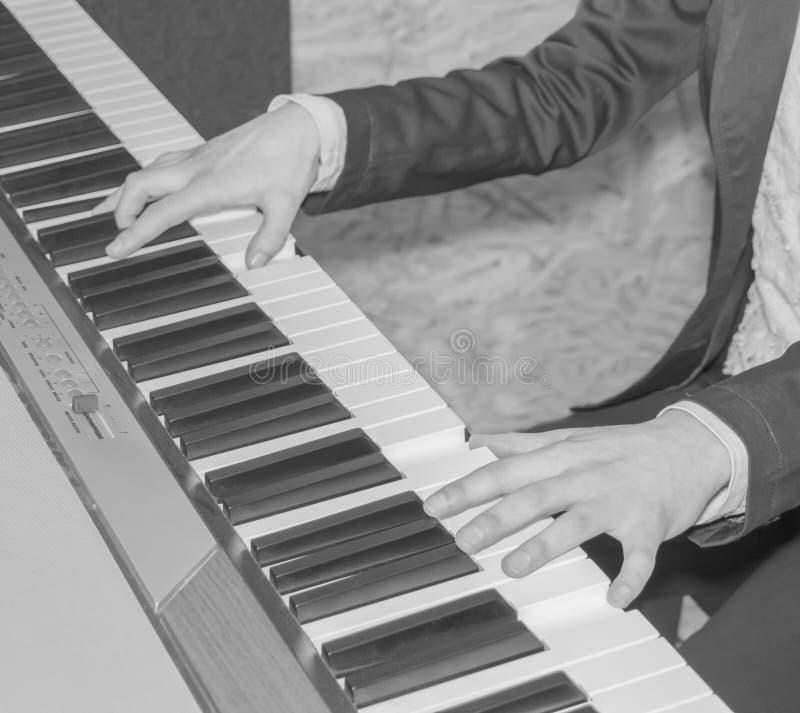 Zwart-witte, Meisjes` s handen op het toetsenbord van de piano stock afbeeldingen