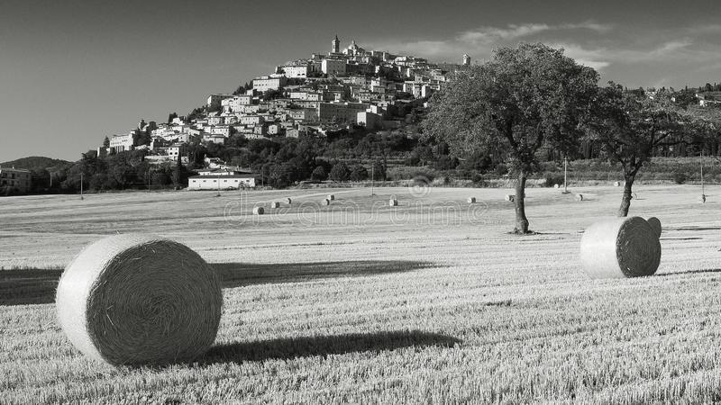 Zwart-witte mening van Trevi in Umbria Italy tijdens de zomer met hooibalen stock foto